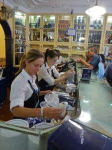Busy staff help customers inside Pastéis de Belém, Portugal's busiest pastry shop, Lisbon, Portugal