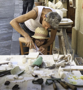 Volterra alabaster craftswoman carver shares her techniques with a young admirer, Volterra, Tuscany, Italy