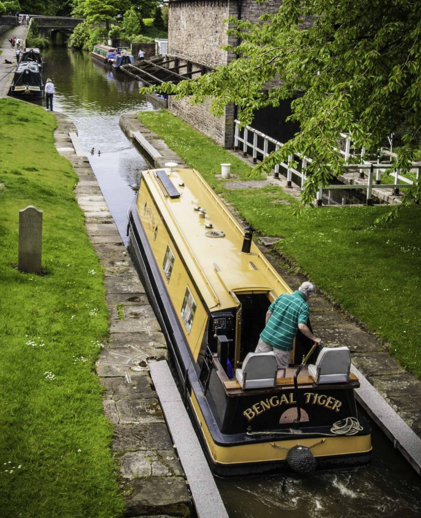 """A brightly colored """"Bengal Tiger"""" emerges from the locks at Marple onto the Macclesfield Canal, Cheshire Ring Canals, Cheshire, UK"""