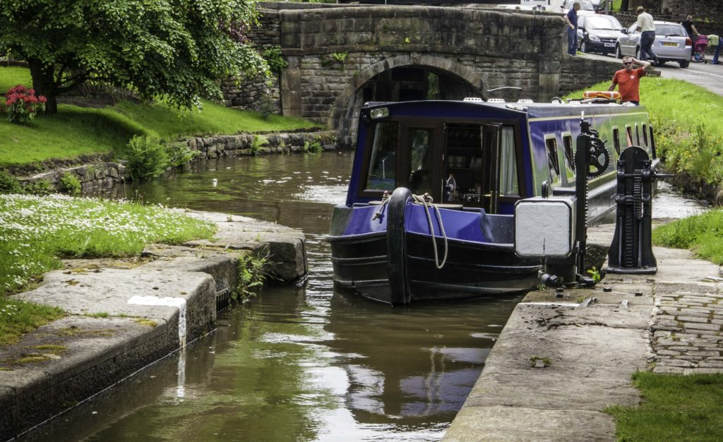 A bit of thoughtful head scratching helps getting a narrow long canal boat into a lock at Marple Junction, Cheshire Ring Canals, Cheshire, UK