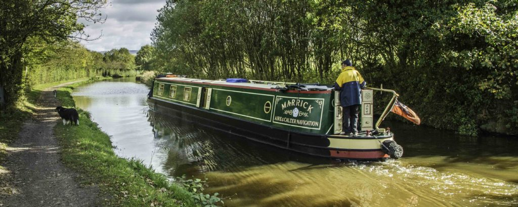 A traditional narrow long boat cruising the Macclesfield Canal, Cheshire Ring Canals, Cheshire, UK