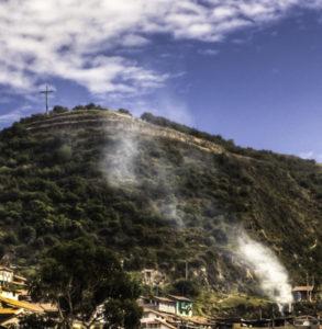 Smoke rises above Cusco to the sacred site of the Inca citadel, Cusco, Peru