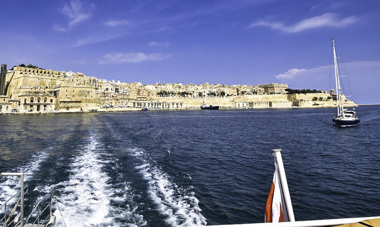 Valletta from the ferry to the Three Cities. The tall, grey, modern structure is the Barrakka Lift that connects the elevated city center with the Harbour.