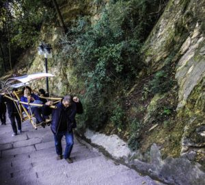 Porters carrying paying passengers to the top of BaidiCheng stairs, White Emperor City, Yangtze River Three Gorges Cruise, Chongqing, China