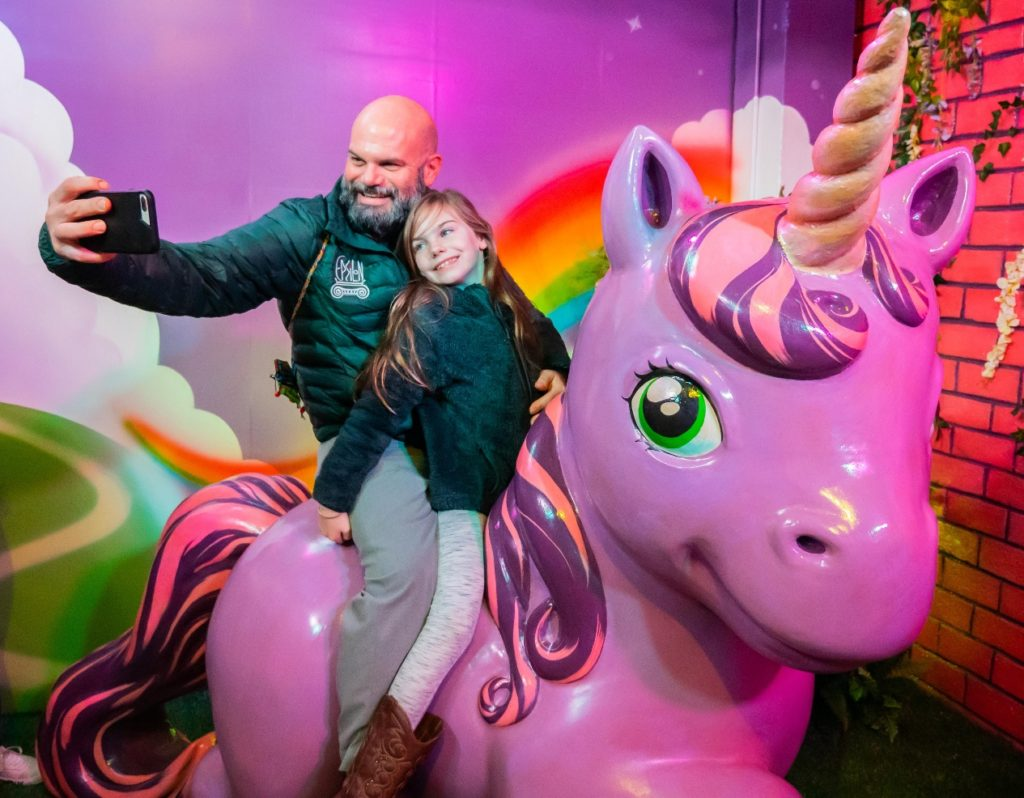 Visitors ride the unicorn, Selfieville, Golden State Theater, Monterey, California