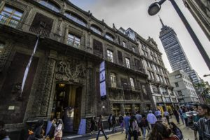 A pedestrian street in the regenerated Centro Histórico, with a colonial era mansion. Torre Latinoamericana is lurking on the right, Mexico City, Mexico