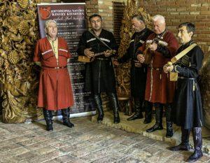 Men in traditional Georgian attire, playing in a winery, T'bilisi, Republic of Georgia